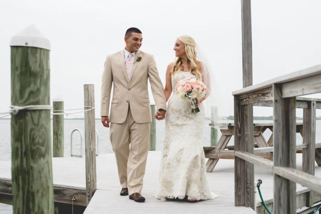 groom in tan suit - bride and groom walking on dock