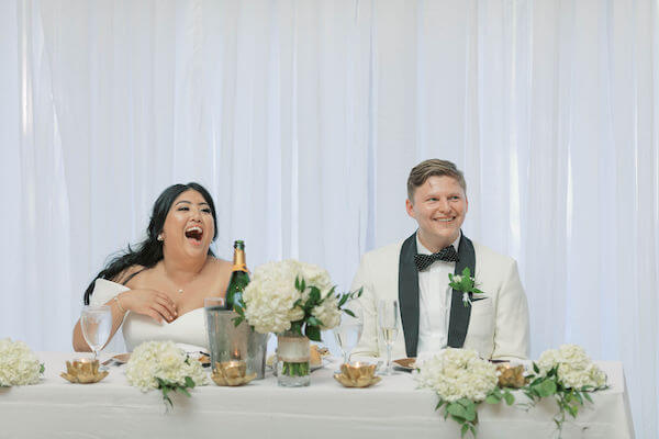 bride and groom laughing - bride and groom drinking champagne - sweetheart table - wedding toasts - funny wedding toasts- St Petersburg wedding - St Petersburg wedding planner - St Petersburg wedding venue - Poynter Institute for Media Studies