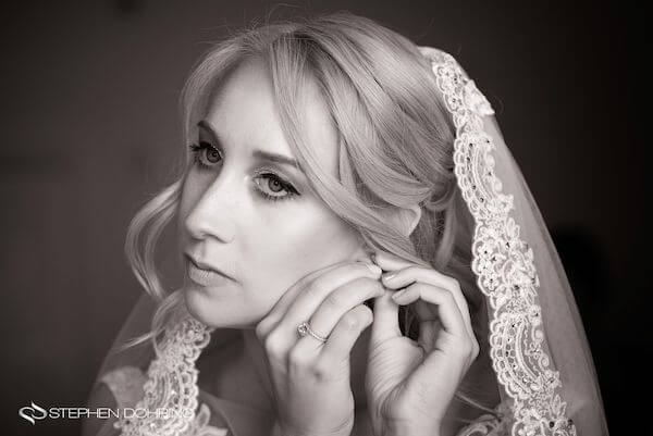 Special Moments Event Planning – Clearwater Beach wedding planner- Sandpearl wedding – Clearwater Beach wedding - bride putting on earring - bride wearing a mantilla