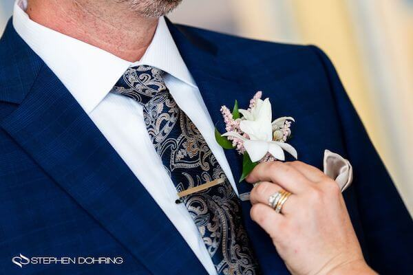 Special Moments Event Planning – Clearwater Beach wedding planner- Sandpearl wedding – Clearwater Beach wedding - groom in Navy blue suit - groom with paisley neck tie- wedding planner pinning on groom's boutonniere