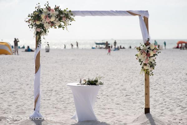 Special Moments Event Planning – Clearwater Beach wedding planner- Sandpearl wedding – Clearwater Beach wedding - wedding structure on beach - wedding arch with pink flowers- wedding arch with pink flowers on beach