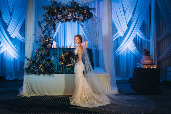 Special Moments Event Planning – Marry Me Tampa Bay – styled wedding shoot – romantic wedding – Hotel Alba – Tampa Wedding – Tampa Wedding planner – dramatic ballroom - sweetheart table - bride - dramatic wedding decor - dark blue wedding lighting - dramatic wedding lighting
