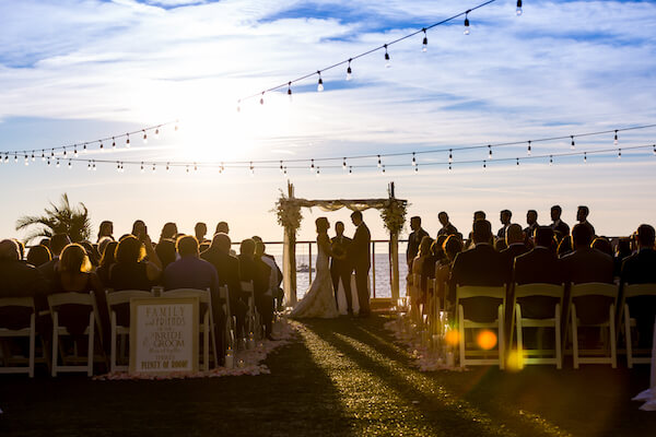 Clearwater Beach Wedding – Opal Sands Wedding – Special Moments Event Planning - Opal Sands wedding ceremony - sunset wedding ceremony - aisle filled with rose petals and candles - Clearwater Beach wedding with wedding arch - bride and groom exchanging wedding vows at sunset