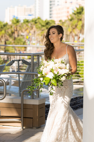Clearwater Beach Wedding – Opal Sands Wedding – Special Moments Event Planning - bride- bride in modern lace wedding gown - wedding gown with rhinestone spaghetti straps - bride with pink and white bouquet - bride walking up behind groom - first look