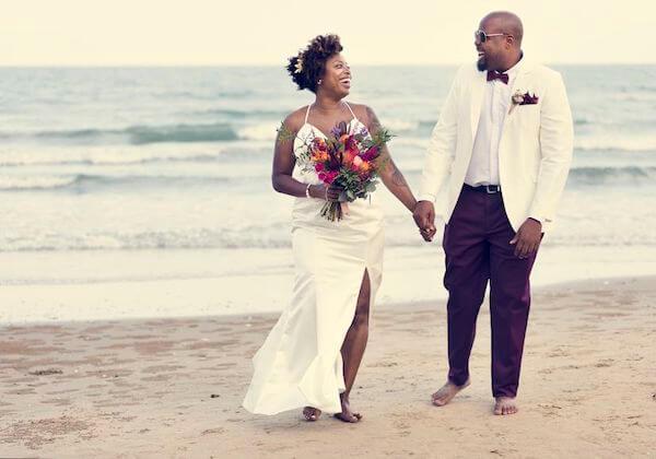 couple walking on a beach - wedding dress for a beach wedding - tips for picking the right wedding dress