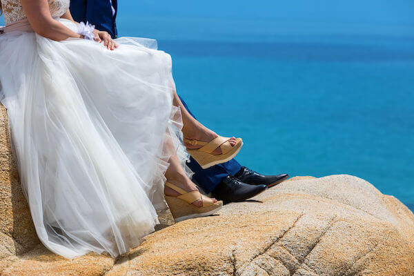 wedding shoes - wearing the right shoes for your gown fitting - alterations on your wedding dress- bride and groom sitting on a rock - shoes of bride and groom