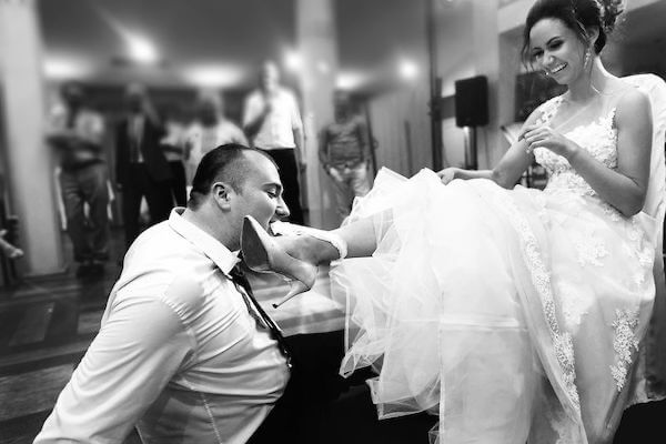 gater toss - wedding reception - planning your wedding reception - groom removing garter from bride's leg with his teeth
