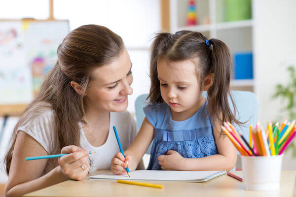 nanny service at a wedding drawing with a little girl - how to include children in your wedding