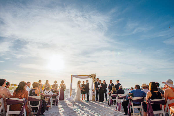 Special moments Event Planning x- Clearwater Beach wedding - Clearwater Beach wedding planner - Sandpearl Resort wedding - beach wedding ceremony. - Clearwater Beach wedding ceremony - bride and groom exchanging wedding vows - sun peaking through the clouds as bride and groom exchange wedding vows