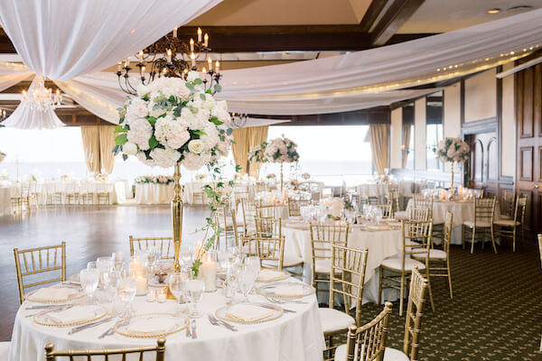Tampa wedding - Tampa wedding reception - Rusty Pelican Restaurant - Rusty Pelican Restaurant wedding - Rusty Pelican Restaurant wedding reception - gold and white wedding reception - draped ceiling with twinkle lights- gold chiavari chairs - white centerpieces on gold risers - gold beaded glass charger plates