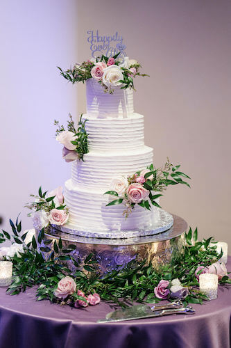 Special moments Event Planning x- Clearwater Beach wedding - Clearwater Beach wedding planner - Sandpearl Resort wedding - wedding cake. - four tiered wedding cake - white butter cream wedding cake - wedding cake on silver cake stand - wedding cake with pink and purple flowers