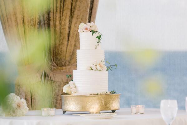 Tampa wedding - Tampa wedding reception - Rusty Pelican Restaurant wedding reception - butter cream wedding cake - wedding cake - three tiered wedding cake - three tiered white wedding cake - wedding cake on gold riser -
