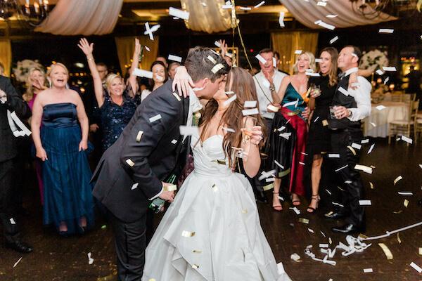 Tampa wedding - Tampa wedding reception - Rusty Pelican Restaurant wedding reception - bride and groom kissing - bride and groom on dance floor - bride and groom kissing on dance floor - bride and groom under confetti shower - confetti cannon