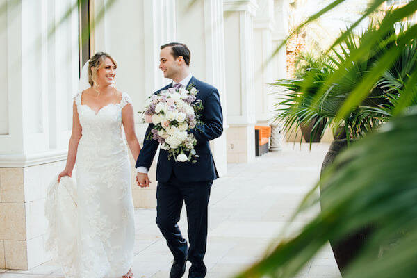 Special moments Event Planning x- Clearwater Beach wedding - Clearwater Beach wedding planner - Sandpearl Resort wedding - first look - bride and groom walking holding hands - groom carrying brides bouquet - first look