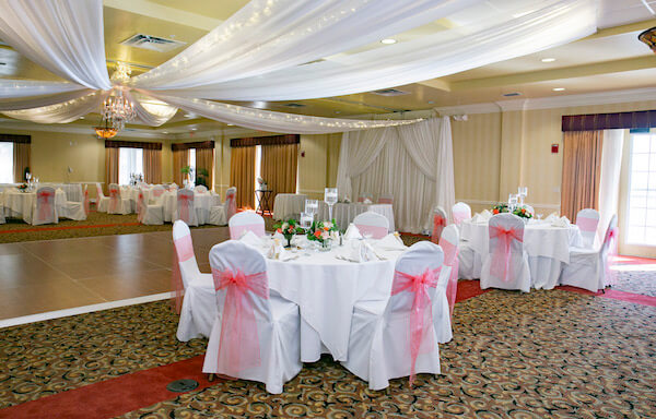 peach and white wedding - draped ceiling with twinkle lights- white chair covers with peach sashes