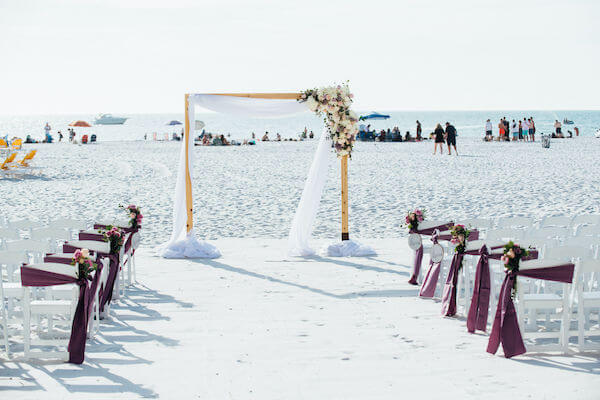 Special moments Event Planning x- Clearwater Beach wedding - Clearwater Beach wedding planner - Sandpearl Resort wedding - beach wedding ceremony - beach wedding ceremony with purple decor - white garden chairs - chairs with purple sashes - wooden arbor with flowers- Gold of Mexico wedding