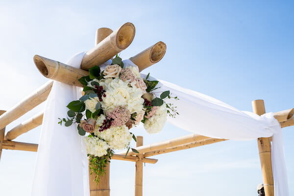 wedding structure - bamboo wedding arch - pink and white ceremony flowers - beach wedding ceremony