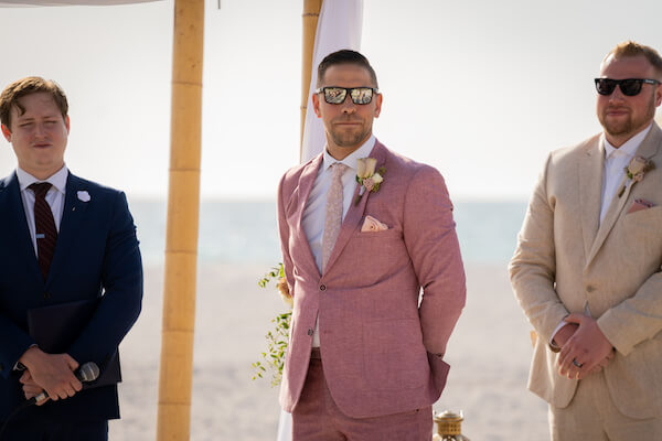 groom in rose colored suit - groom waiting for bride- groom standing on beach waiting for bride - Florida beach wedding