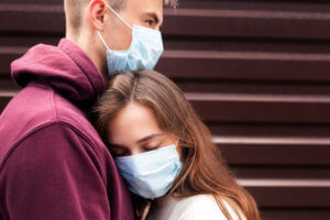 couple hugging while wearing face masks - engaged couple wearing face masks - postponing your wedding during COVID 19 - assistance rescheduling your wedding