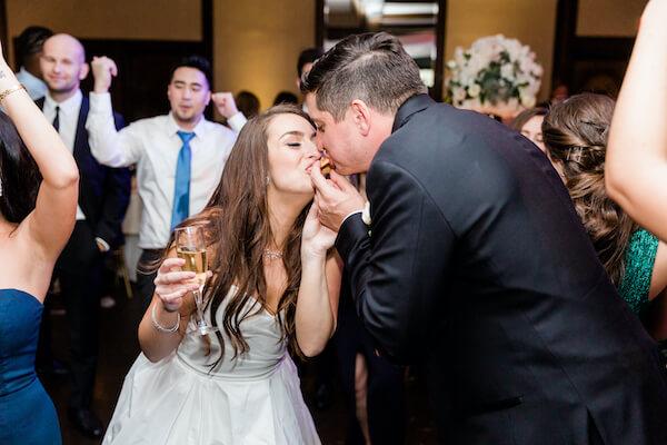 bride and groom eating late night snacks on the dance floor