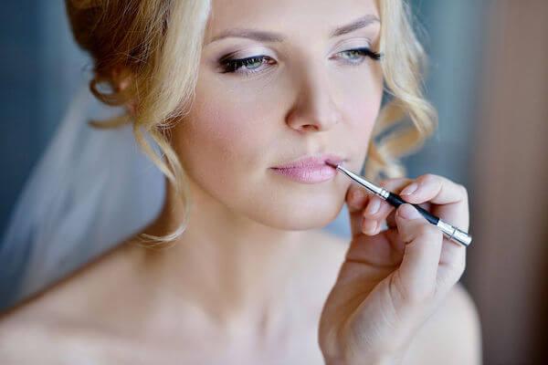 makeup artist applying bride's lipstick -