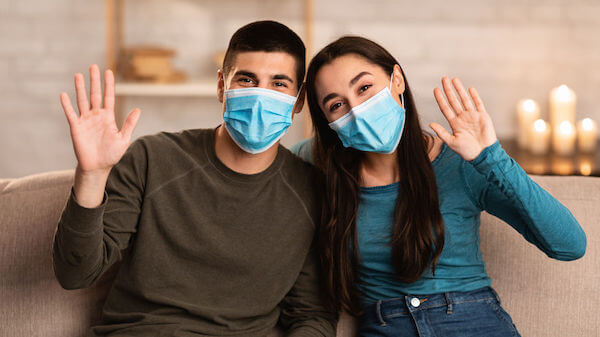 Smiling couple wearing surgical face mask - safety protocols for weddings during COVID