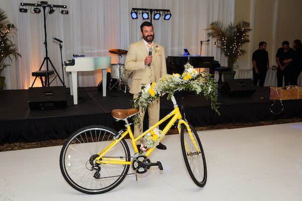 groom presenting his bride with a yellow bicycle just like the ones they rode on their first date