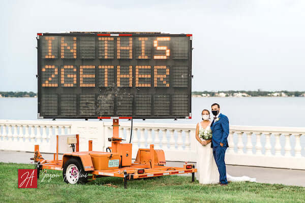 """masked Tampa bride and groom standing next to COVID """"in this 2gether' sign along the road."""
