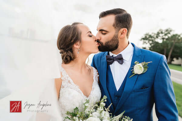 bride and groom kissing next to Tampa Bay