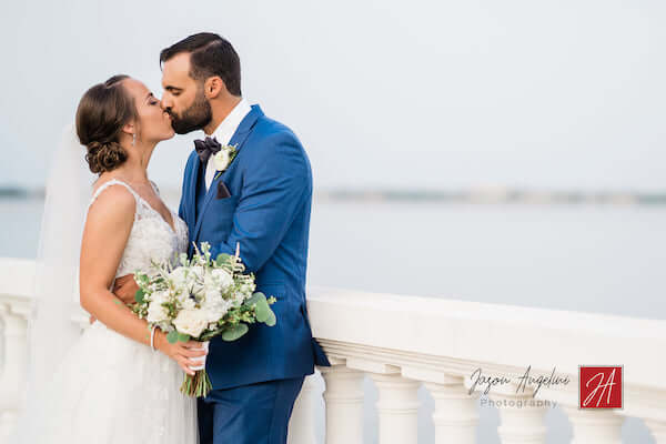 bride and groom kissing in photo on Bayshore Boulevard  next to Tampa Bay