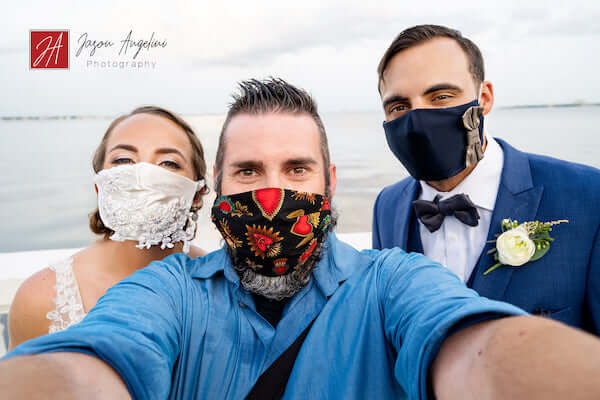 bride and groom wearing custom COVID-19 wedding masks pose for a selfie with photographer Jason Angelini
