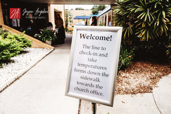 Sign at church sharing COVID precautions for wedding ceremony