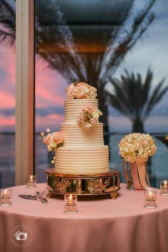 Tampa weddings – wedding cakes – cake stands – displaying your wedding cake - white wedding cake on a silver stand in front of a window at sunset