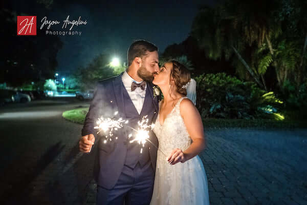 bride and groom with sparklers kiss goodnight