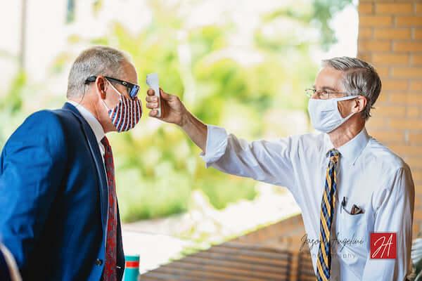 Church volunteer taking wedding guests temperature before wedding ceremony