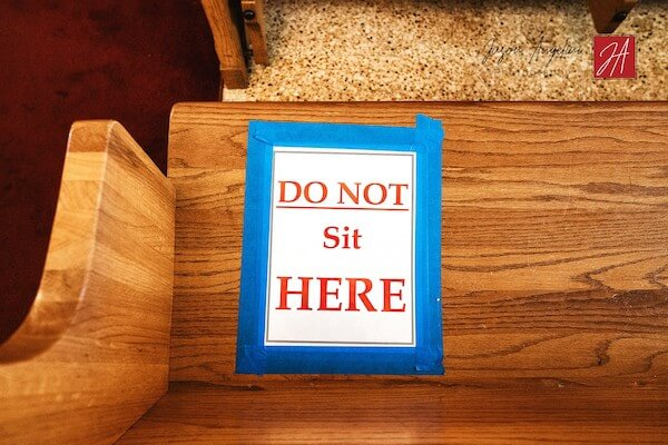 DO NOT Sit HERE sign blocks off pews to promote social distancing