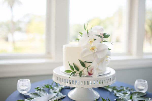 Intimate white wedding cake on a white cake stand