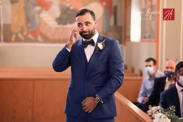 groom crying as socially distant wedding guest wearing mask watch bride's arrival