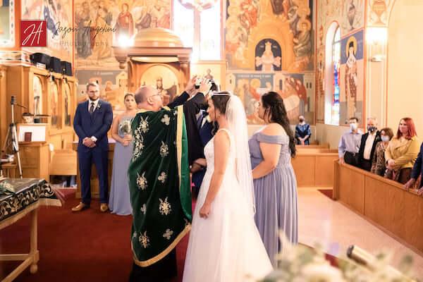 bride and groom wearing crowns in Gree  social distancingwhile practicingk Orthodox wedding