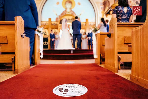 Social distancing stickers  on church's aisle during Tampa wedding ceremony