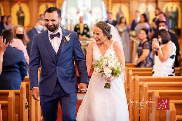 Newlyweds walking u church aisle as guests wearing COVID masks look on
