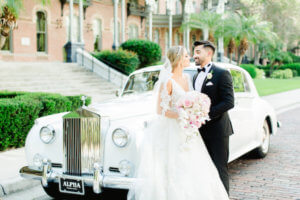 Tampa bride and groom in front of a white Rolls Royce