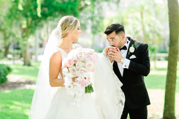 Groom kissing brides hand while walking in a park