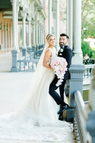 bride and groom leaning against a metal railing on the porch of the University of Tampa