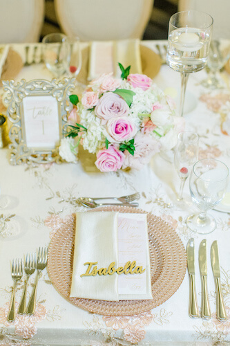 rose gold charger plates on a lace embroidered table cloth with a pink and white floral centerpiece