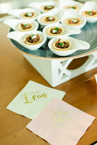 individually plated passed hors d 'oeuvres next to monogrammed cocktail napkins