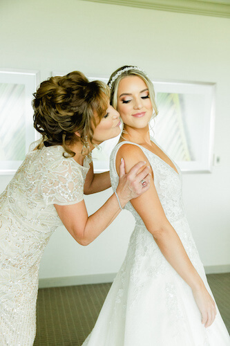 Mother of the bride kissing her daughter on the cheek as she finishes getting dressed