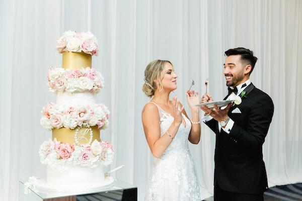 bride and groom feeding each other wedding cake