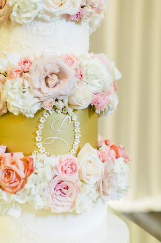 cold and champagne wedding cake with monogram and pink and blush flowers