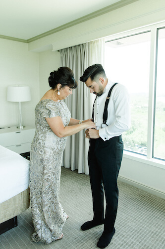 Mother of the groom assisting him in getting dressed